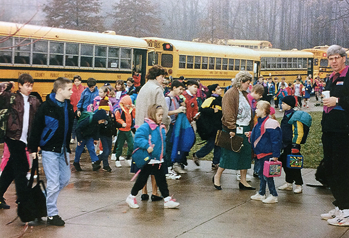 Photograph of students arriving at the start of the school day at Forestville. School buses are parked along the sidewalk in front of the building, and children are walking toward the front doors of the school.
