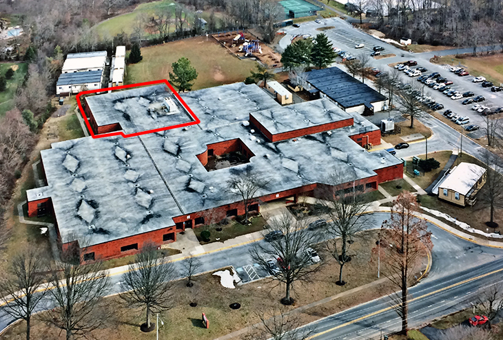 Aerial photograph of Forestville Elementary School. The building is seen from a vantage point above Utterback Store Road, looking east. Several trailers and modular buildings are visible around the school. A portion of the rear of the building has been highlighted with a red outline.