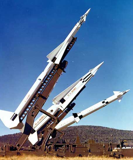 Color photograph of three types of Nike missiles on launchers.